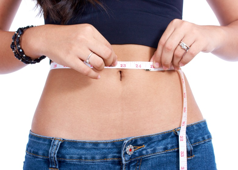 Girl Using A Tape Measure Checking Her Waistline